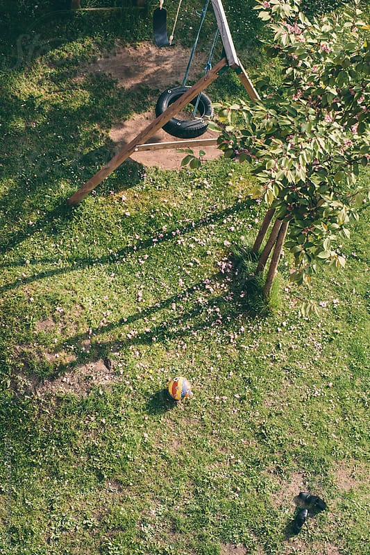 Rubber ball and shoes on the grass by Lior + Lone for Stocksy United