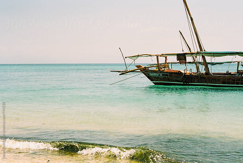 Traditional wooden dhow anchored alongside a Zanzibar beach by Helen Rushbrook for Stocksy United