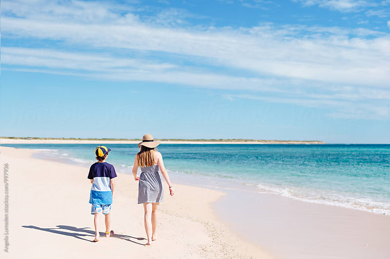 Two children walking together at the beach on the Ningaloo Coast in Western Australia by Angela Lumsden for Stocksy United