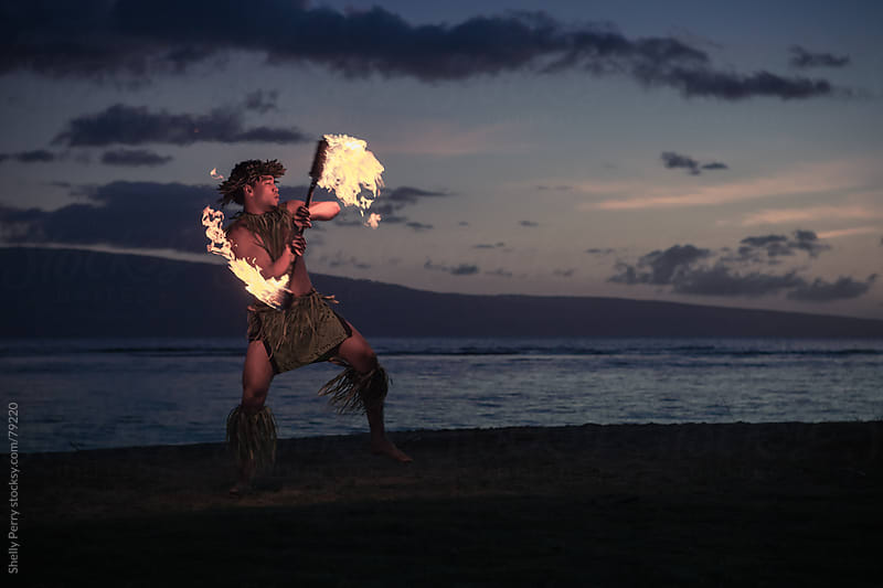 Traditional Hawaiian Fire Dancer twirling and tossing his flaming torch. by Shelly Perry for Stocksy United