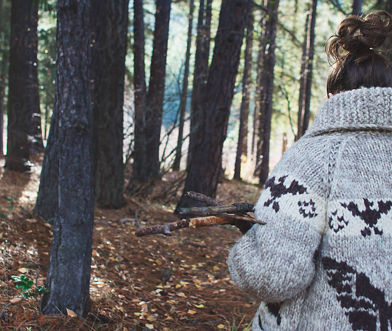 young woman in wool sweater gathering branches in forest by Tana Teel for Stocksy United