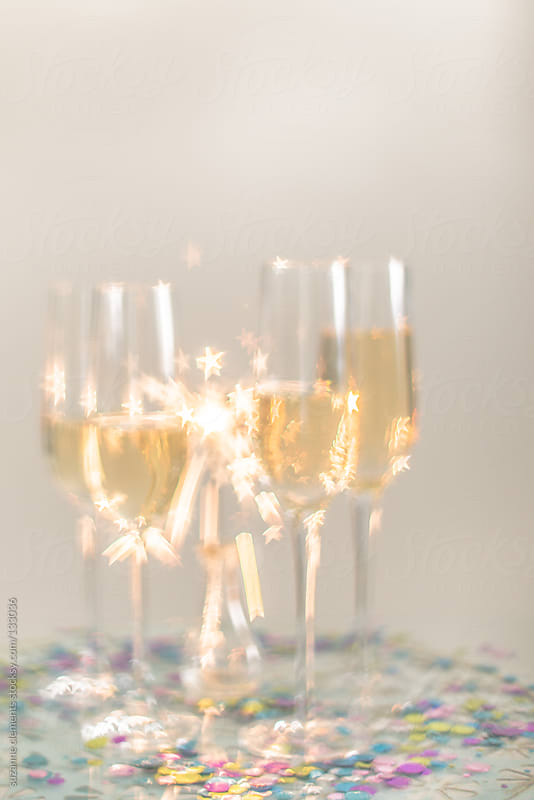 Starry Sparkler Glimmers behind Champagne Flutes by suzanne clements for Stocksy United