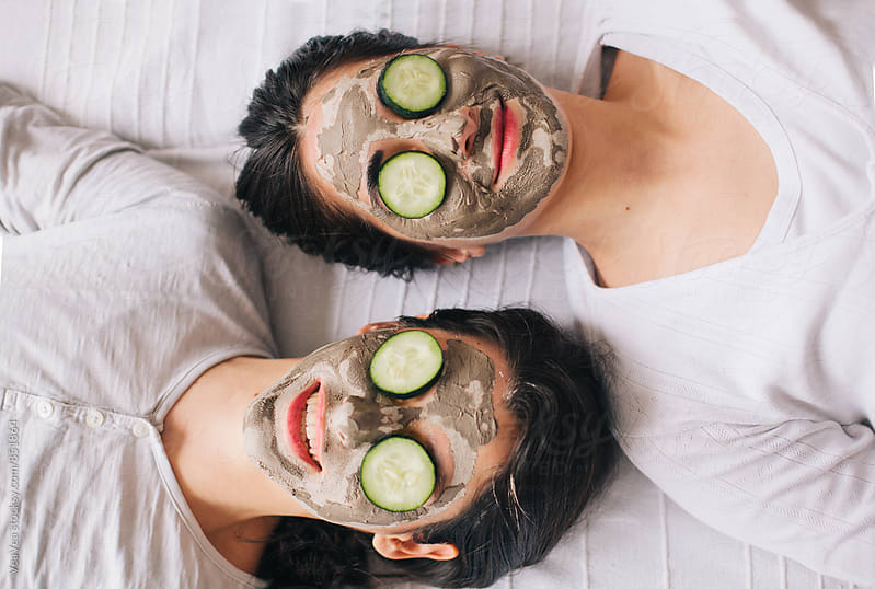 Two beautiful women with facial masks and cucumbers on their faces by Marija Mandic for Stocksy United