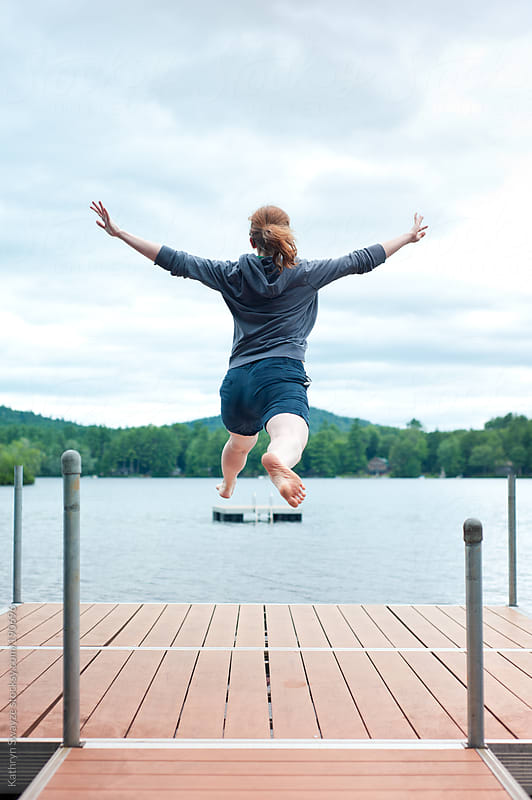 Woman jumping on lakeside dock with trees and raft in background by Kathryn Swayze for Stocksy United