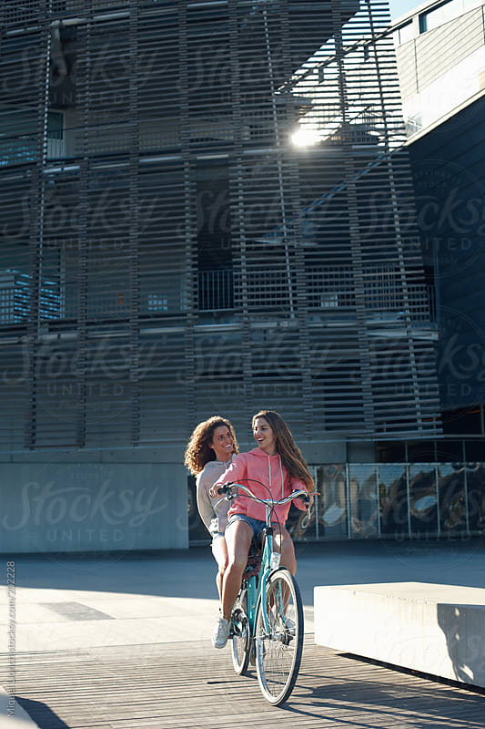 Two young girls  riding a bike in a modern district of Barcelona city by Miquel Llonch for Stocksy United