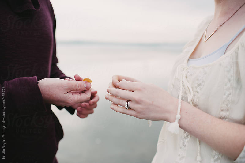 couple holding sea shells on cloudy beach by Kristin Rogers Photography for Stocksy United