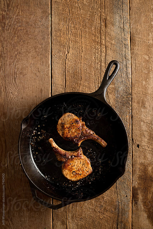 Cooked Pork Chops in Skillet on Wood by Jeff Wasserman for Stocksy United