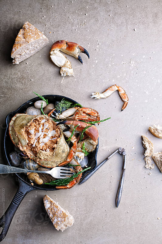 Dressed crab served with crusty bread. Crab meal in a skillet. by Darren Muir for Stocksy United