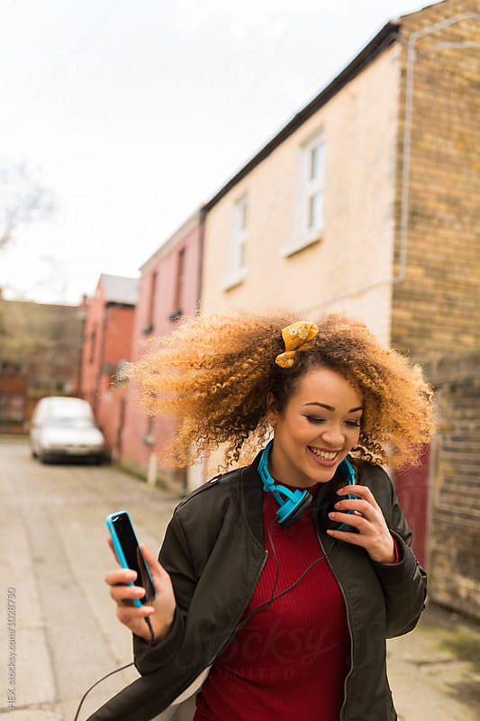Afro american woman with and blue headphones smiling in outdoors. by HEX. for Stocksy United