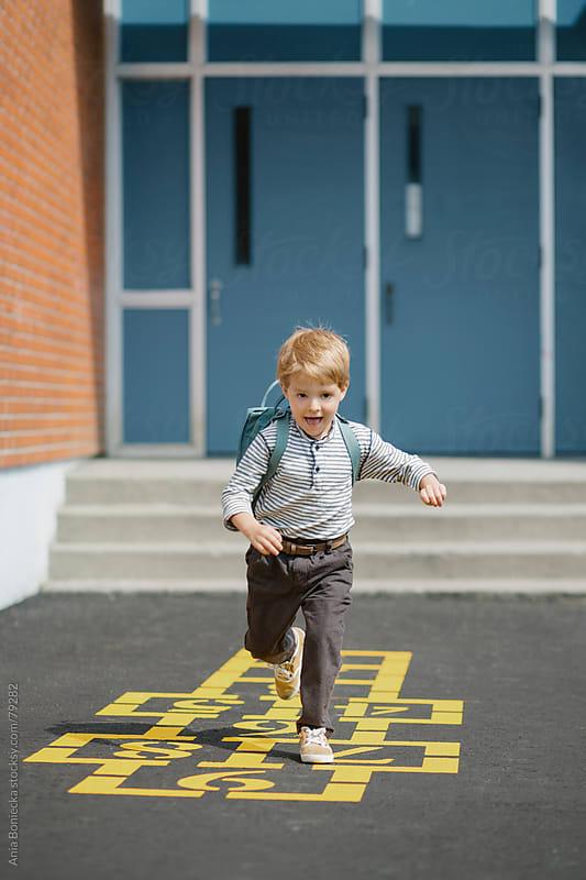 Blonde boy running across a hopscotch in a school playground by Ania Boniecka for Stocksy United