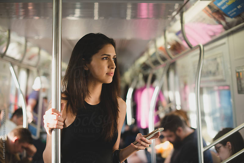 Young woman riding subway train in the city by Lauren Naefe for Stocksy United