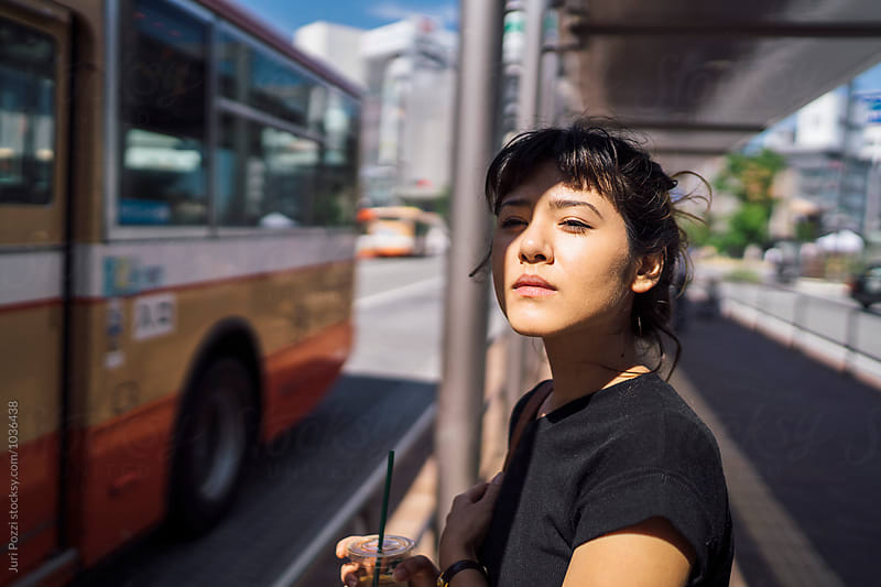 Japanese young woman at a bus stop in Japan by Juri Pozzi for Stocksy United