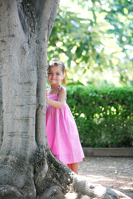 Little girl in pink and white gingham dress peeking out from behind a tree by Dina Giangregorio for Stocksy United