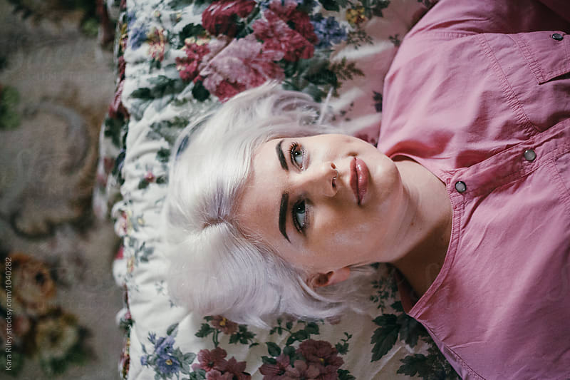Blonde woman lying on floral bed by Kara Riley for Stocksy United