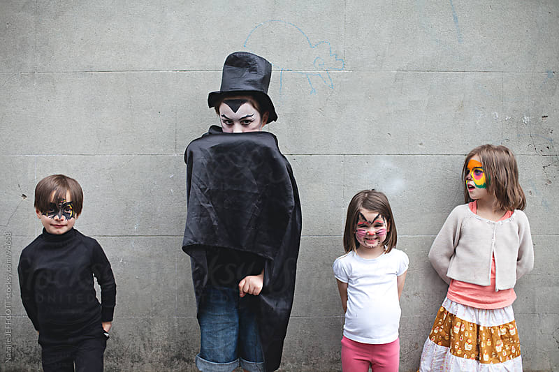 young children waiting to go trick or treating at Halloween by Natalie JEFFCOTT for Stocksy United