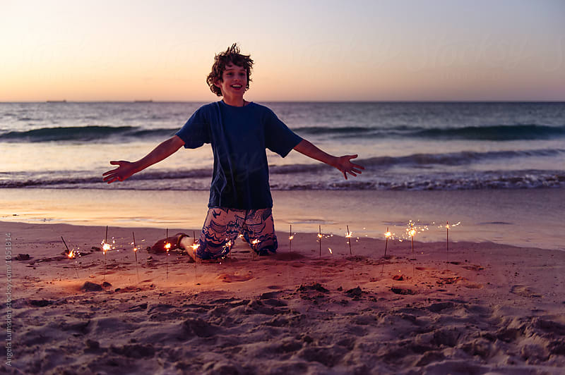 Happy boy with outstretched arms and sparklers at the beach after sunset by Angela Lumsden for Stocksy United