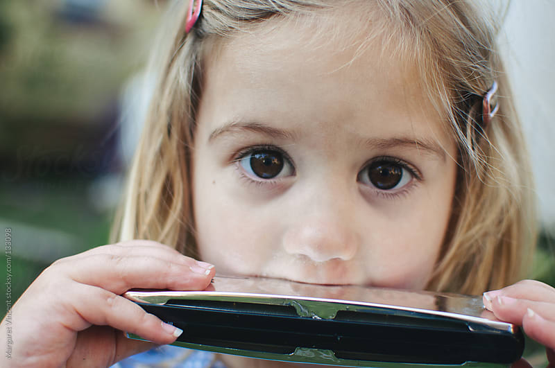little girl playing a harmonica by Margaret Vincent for Stocksy United