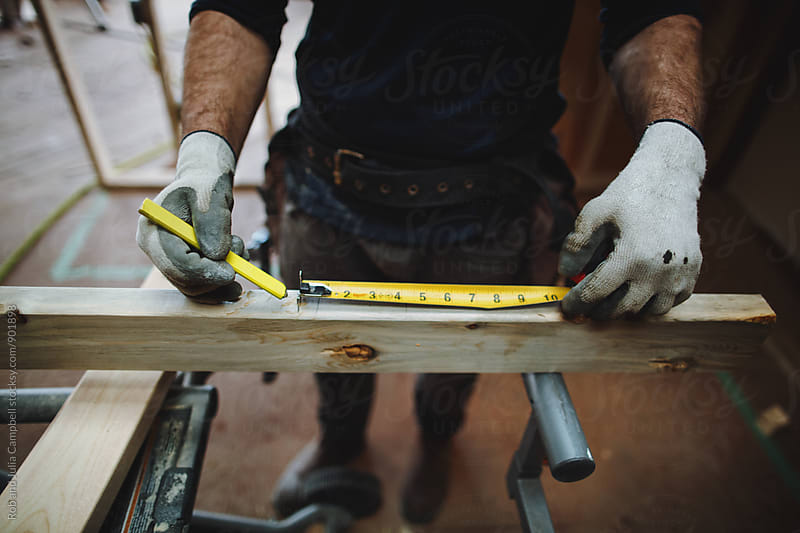 Carpenter hands measuring two by four - 2X4- wood inside  by Rob and Julia Campbell for Stocksy United