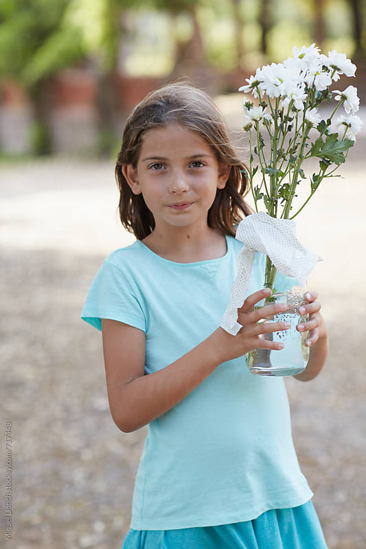 Young girl holding a jar with flowers by Miquel Llonch for Stocksy United