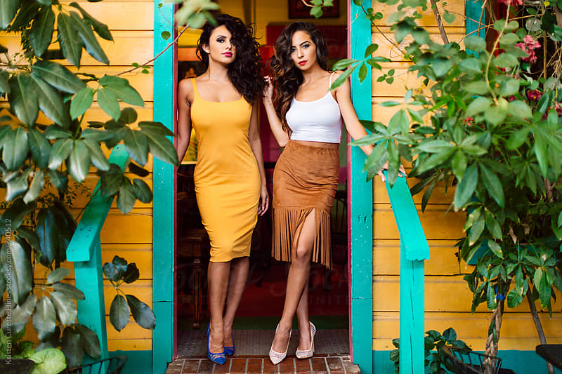 Two beautiful Spanish women posing on a colorful patio by Kristen Curette Hines for Stocksy United