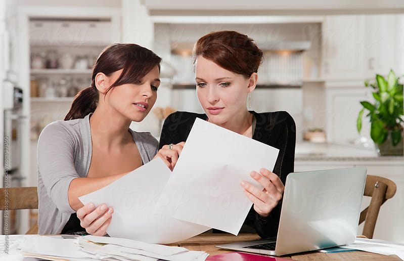 Two women doing paper work at home by Andersen Ross Photography for Stocksy United