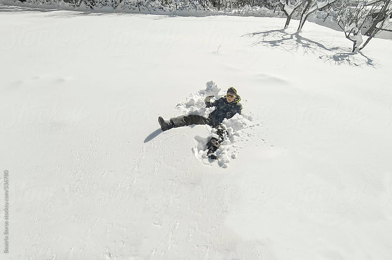 Teenager boy comfortably sitting on the deep snow by Beatrix Boros for Stocksy United