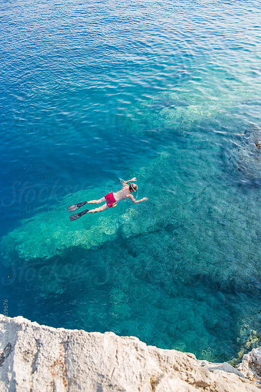 Man snorkeling in blue ocean water on a sunny day  by Jovo Jovanovic for Stocksy United