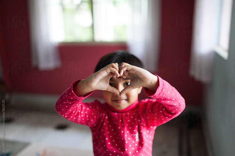 Little girl making heart sign with her hands by Saptak Ganguly for Stocksy United