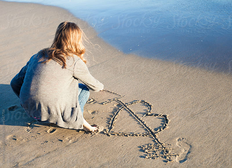 Girl drawing a heart in the sand near the waves by Carolyn Lagattuta for Stocksy United