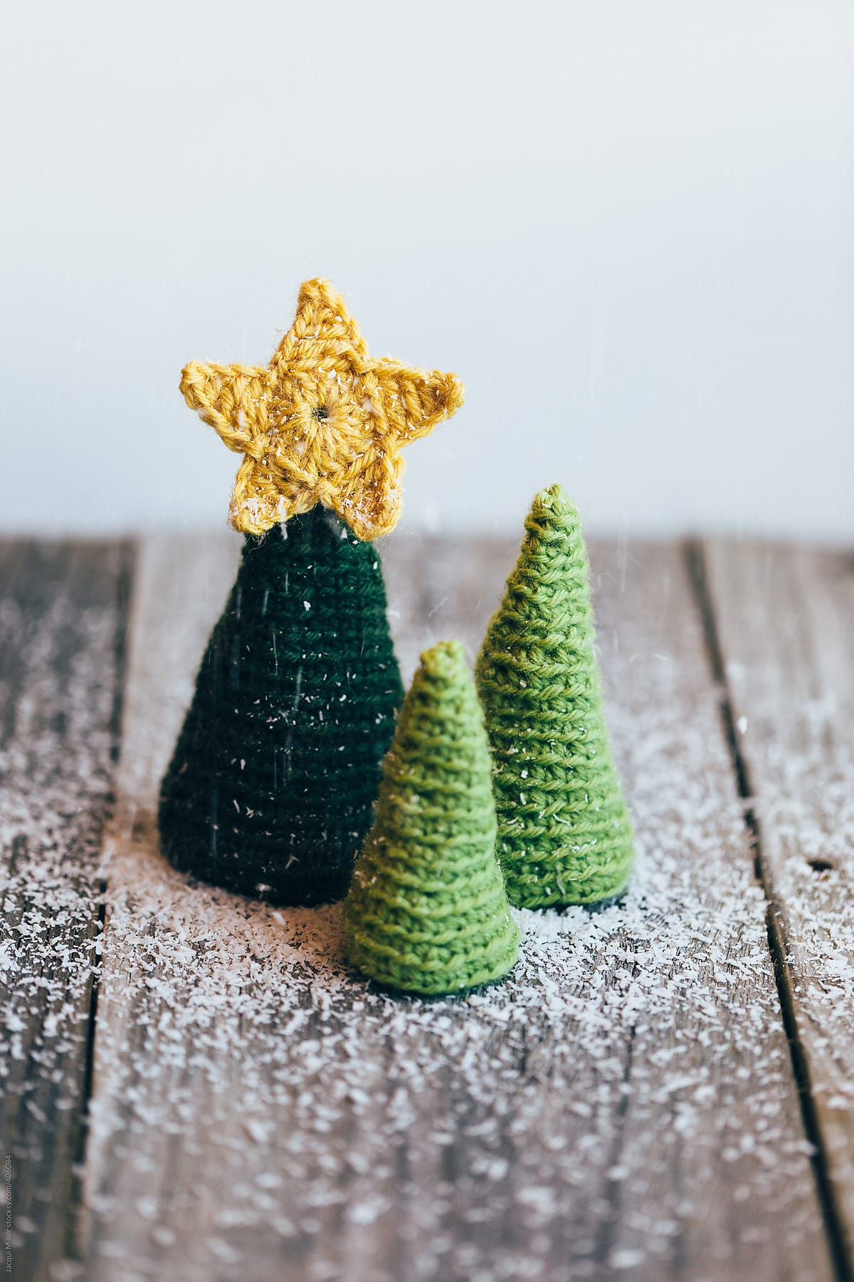 Three Little Crocheted Christmas Trees With Falling Artificial Snow On A Rustic Wooden Table By Jacqui Miller Christmas Xmas Stocksy United