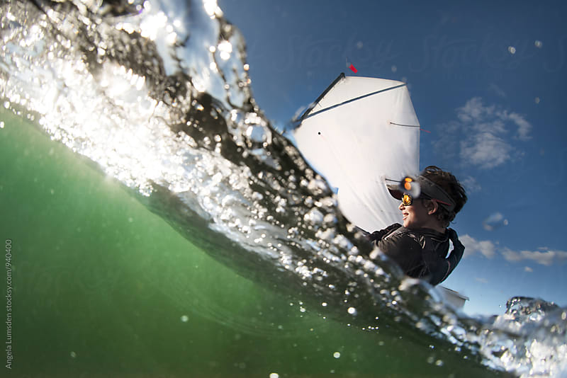 Over under close up image of a boy sailing an optimist class dinghy by Angela Lumsden for Stocksy United