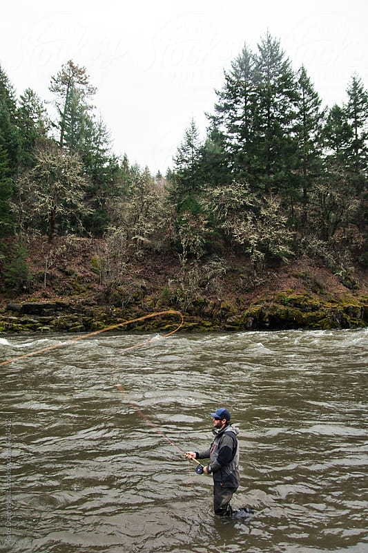 Man stands in the river casting an orange fly fishing line. by Kate Daigneault for Stocksy United