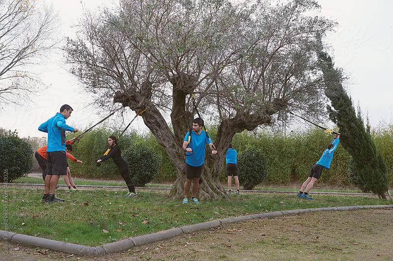 group of young people doing some exercise at park by Guille Faingold for Stocksy United