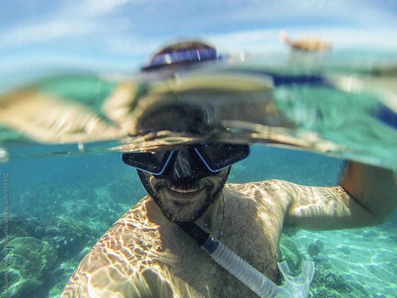 Underwater self portrait of a man snorkeling with diving mask by Alejandro Moreno de Carlos for Stocksy United