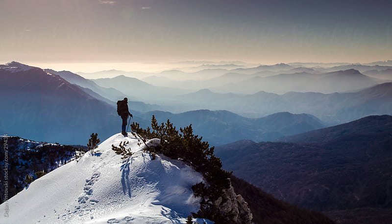 Man standing on a mountain by Dejan Ristovski for Stocksy United