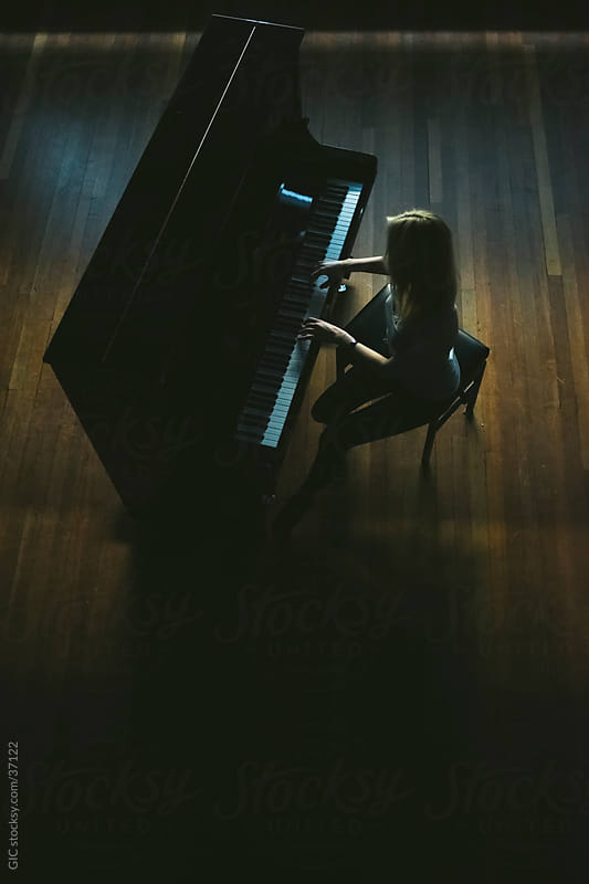 Woman playing a piano by Simone Becchetti for Stocksy United