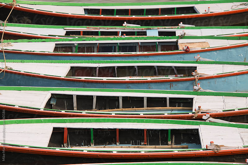 A row of boats tied to each other on the river Ganges in India. by Mike Marlowe for Stocksy United
