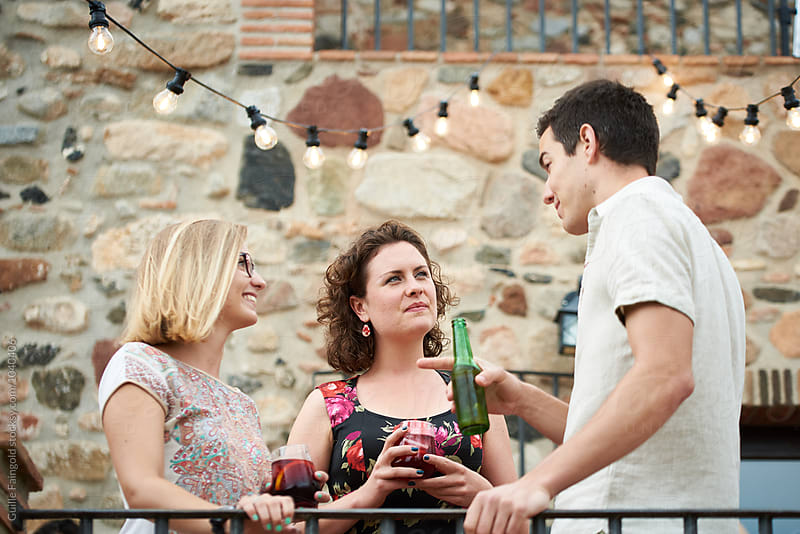Three friends with drinks talking at party by Guille Faingold for Stocksy United