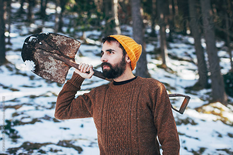 Young lumberjack holding an old shovel in a snowy forest.  by BONNINSTUDIO for Stocksy United