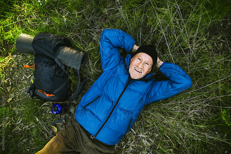 Senior mountaineer resting in the grass from above.  by BONNINSTUDIO for Stocksy United