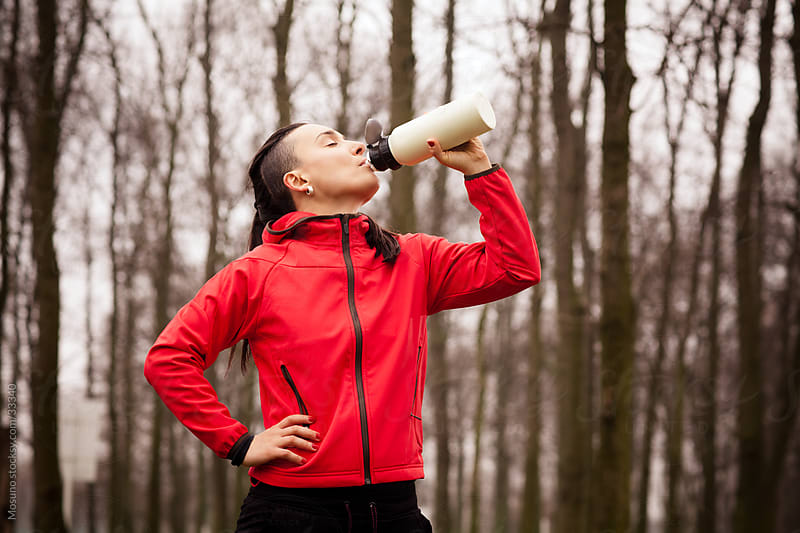 Woman drinking water after jogging in the park. by Mosuno for Stocksy United