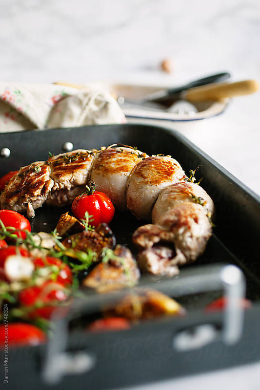 Roast pork tenderloin in an oven tray with tomato and figs. by Darren Muir for Stocksy United