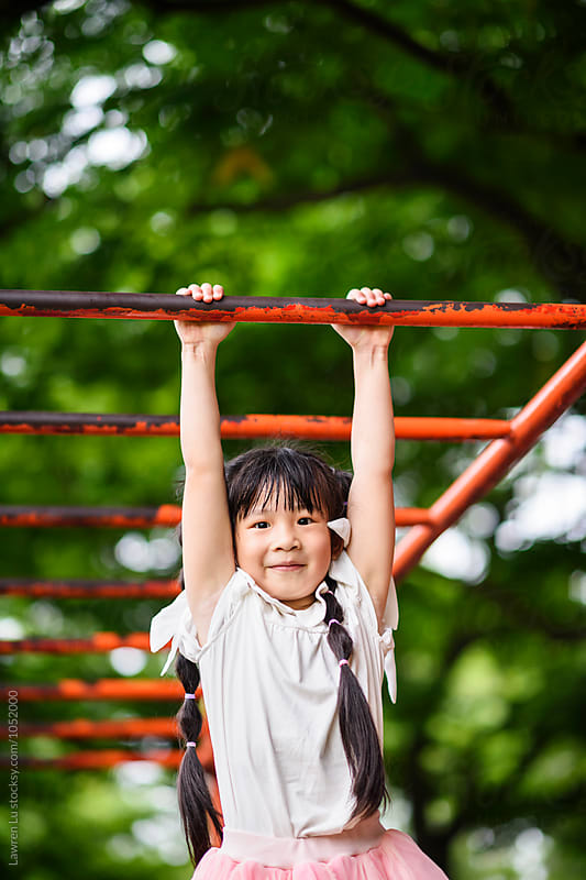 Smiling asian girl hanging on metal bar at playground by Lawren Lu for Stocksy United