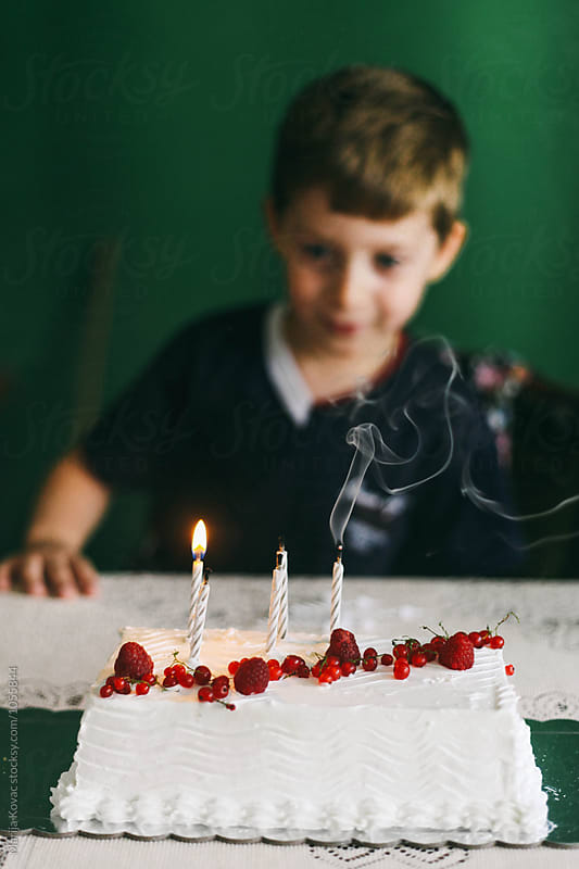 Kid looking at the cake by Marija Kovac for Stocksy United