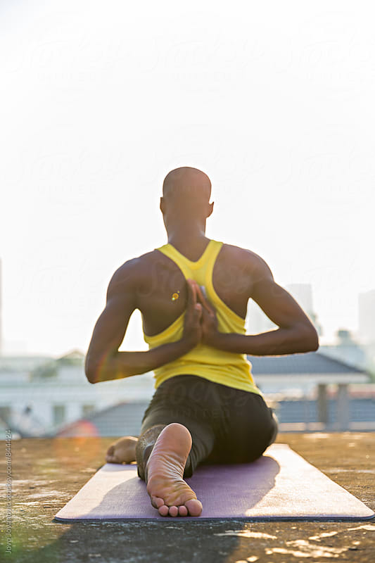 Back of a fit dark skinned man doing yoga on a city building rooftop  by Jovo Jovanovic for Stocksy United