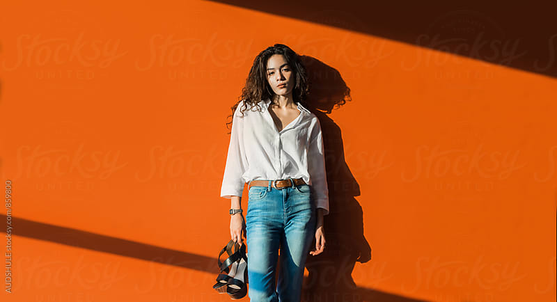 Portrait of beautiful fashionable mixed woman with orange wall in background. by Marko Milanovic for Stocksy United