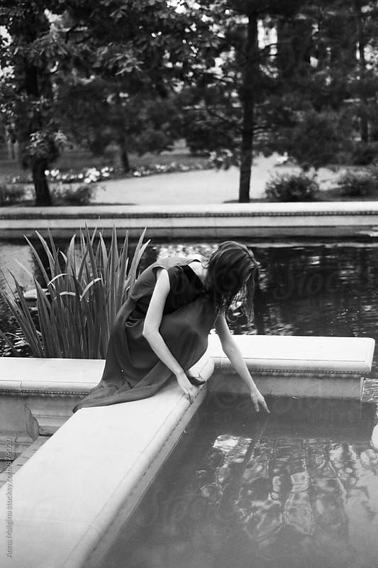 A black and white photo of a young woman touching water in the pond by Anna Malgina for Stocksy United