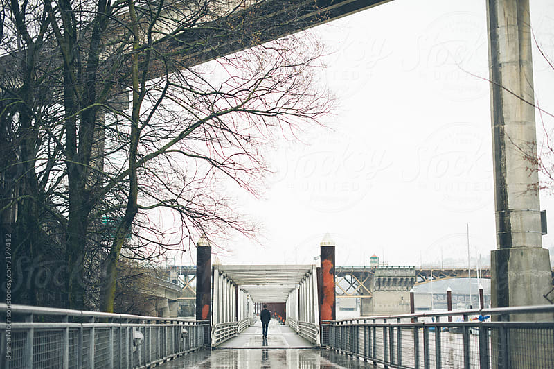 Man Walking in Industrial Area in Portland by Briana Morrison for Stocksy United