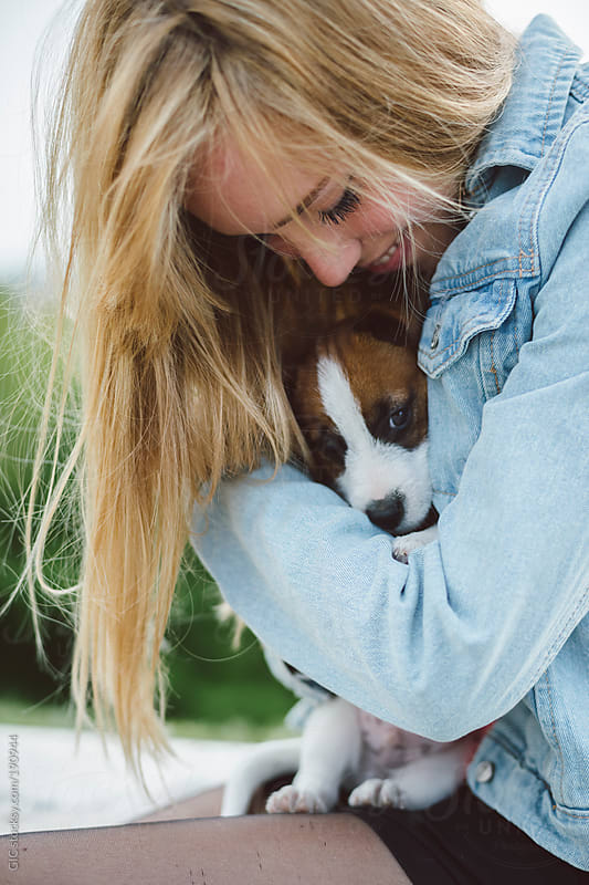 Young beautiful blonde woman embracing her puppy by GIC for Stocksy United