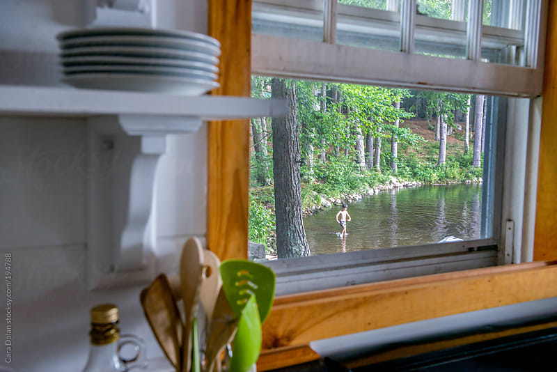 View from the kitchen window - child splashing in a lake outside by Cara Dolan for Stocksy United